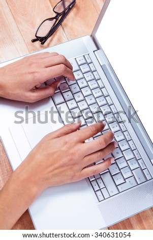 Feminine hands typing on laptop with glasses on table