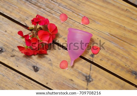Feminine hygiene product - Menstrual cup next to a beautiful red flowers, in a wooden background
