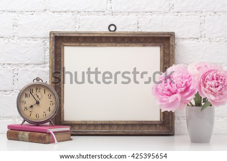 feminine mock-up with vintage photo frame, pink flowers, books and an old alarm clock on a desk - stock photo