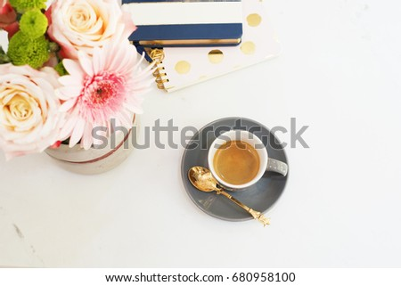 Feminine workplace concept. Freelance fashion comfortable femininity workspace in flat lay style with coffee, flowers, notebooks on white marble background. Top view, bright, pink and gold