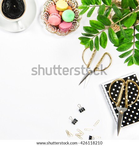 Feminine workplace with coffee, macarons cookies, office supplies and green plant on white table background. Flat lay - stock photo