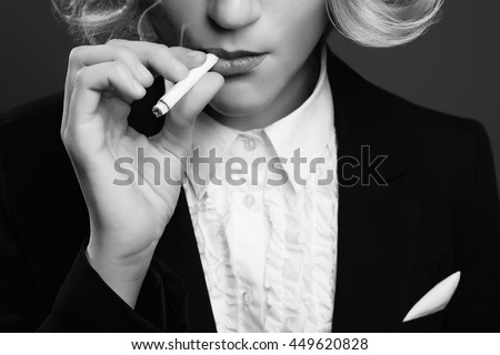 Femme fatale concept. Close up retro portrait of rich young woman smiling wearing expensive luxurious tuxedo and smoking cigarette over gray background. Studio shot