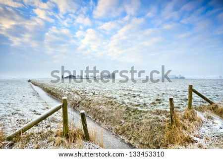 fence and frozen canal during winter in Dutch farmland - stock photo