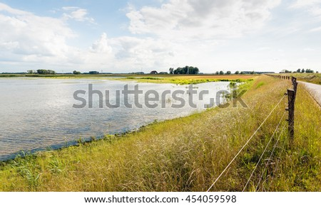 Fence and road on a Dutch dike along a flooded polder area. It is at the end of the afternoon on a sunny day in the summer season. - stock photo