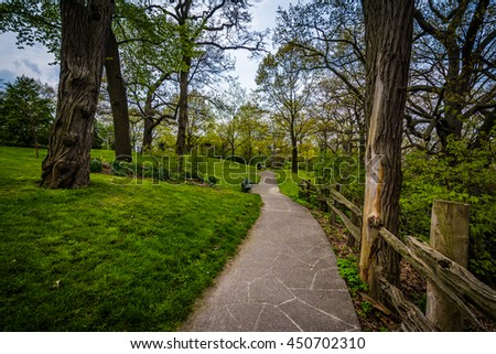 Fence and trees along a walkway at High Park, in Toronto, Ontario. - stock photo