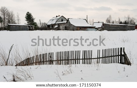 Fence at the village in a snow-covered field. Winter. Russia - stock photo