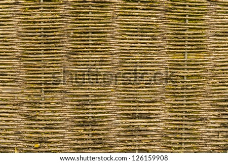 Fence braided made of brown natural wood - stock photo