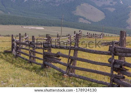 Fence in a mountain valley. A summer landscape. - stock photo