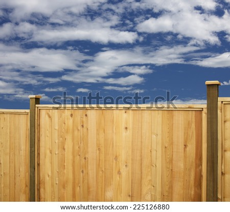 Fence - new wooden fence with sky and clouds - stock photo