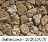 Fence of a natural building material of a yellow shell rock - stock photo