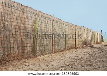 fence of reed in the beach - walkway with barrier on the sand