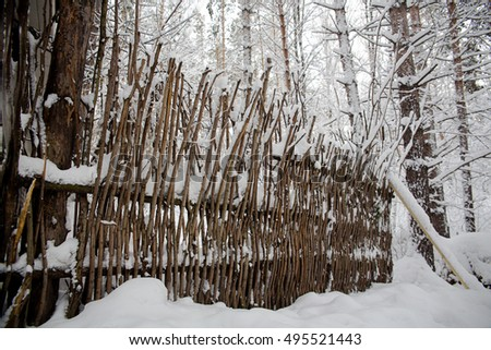 fence of twigs under the snow in the winter