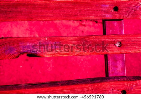 fence of wooden narrow planks with cracked red paint with sunlight and shadows
