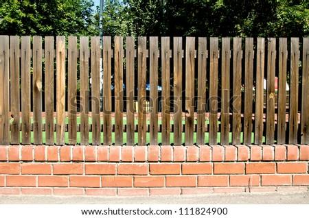 fence of wooden slats on the bricks - stock photo