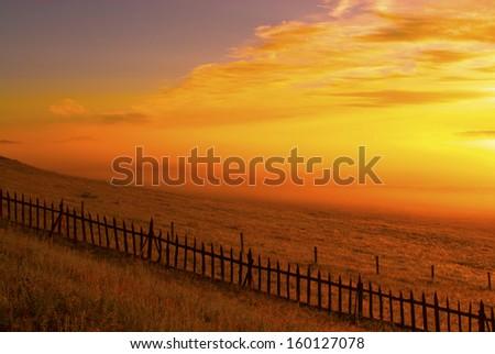 Fence on the prairie - stock photo