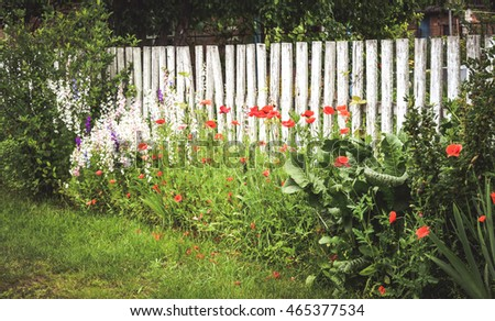 fence white wooden beams, green grass and red flowers
