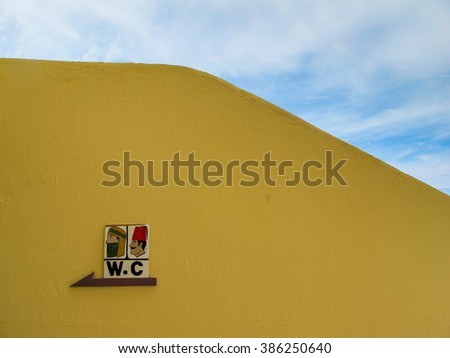 Fence with a WC sign, Egypt Yellow painted fence outdoors with a WC sign. Traditionally dressed man and woman. Egypt.  - stock photo