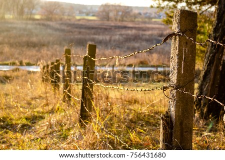 Fence with barbed wire on a sunny day