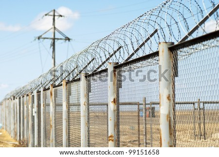 Fence with barbed wire (small depth of sharpness) - stock photo