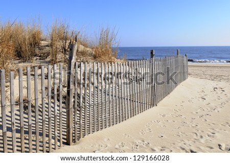 Fence with Sand Dune and Ocean - stock photo