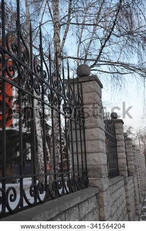 fence, wrought iron fence, forging and stone, wrought-iron ornaments, birch on the background of wrought fence - stock photo