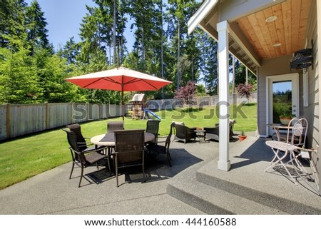 Fenced backyard area with patio table, umbrella and chairs and play set for kids.