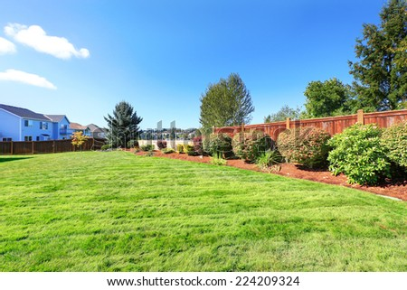 Fenced backyard land with decorative bushes and lawn - stock photo