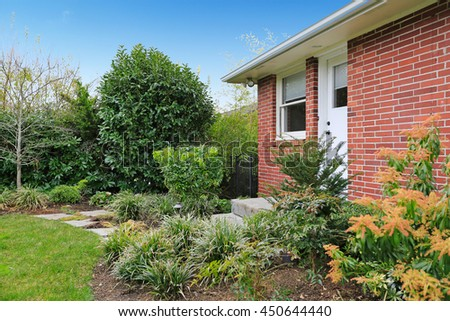 Fenced backyard. View of green lawn and flower beds - stock photo