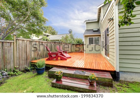 Fenced backyard view. View of deck with red chairs after rain. - stock photo