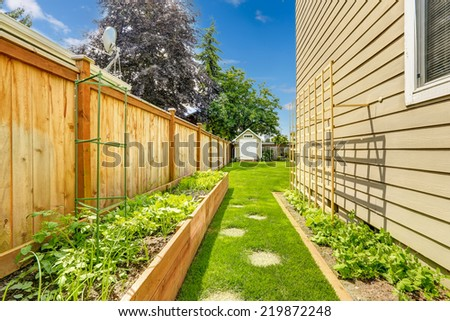 Fenced backyard with garden bed and green lawn - stock photo