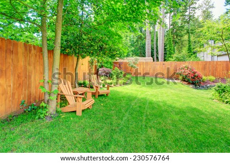 Fenced backyard with green lawn, flower beds and romantic sitting area with wooden chairs and table - stock photo