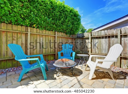 Fenced backyard with small patio area. Tile floor and green bushes. Northwest, USA