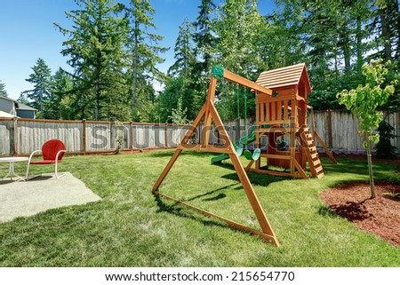 Fenced backyard with wooden playground for kids