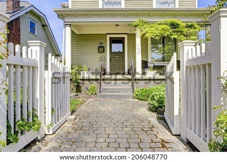 Fenced front yard with open gate. View of entrance porch with walkway