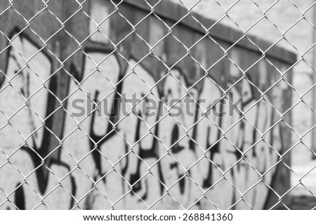 Fenced industrial park with graffiti wall.  - stock photo