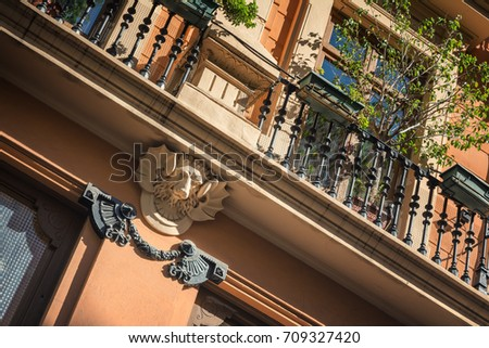 Fenced narrow balcony (balconet) with a tree, flower pots and a lion head sculpture decoration on the wall - fragment of an apartments building