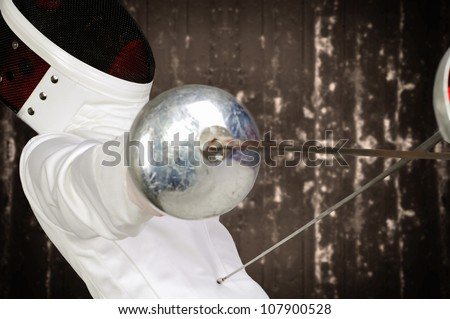 fencer athlete with sword and mask in action - stock photo