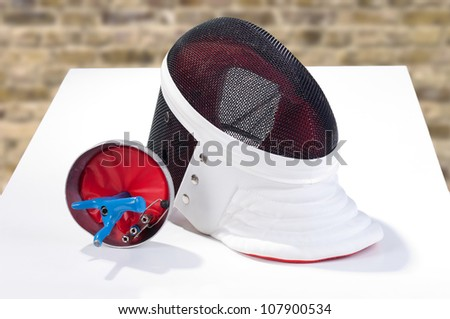 Fencer sword and mask on a table - stock photo
