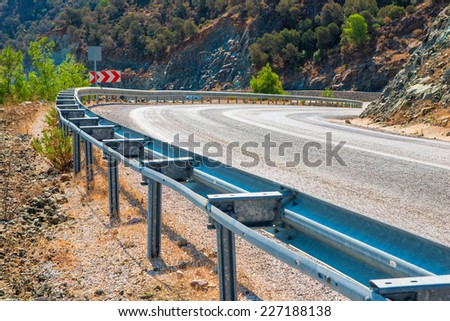fencing dangerous bend of the mountain road - stock photo