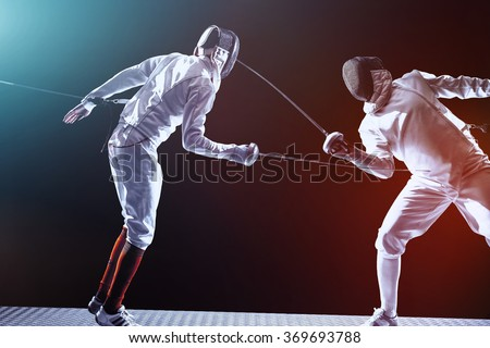 Fencing players isolated on black background - stock photo