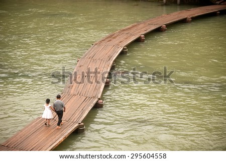 FENGHUANG, CHINA - JUNE 9 : Villagers walking on bridge of the old town on June 9, 2015 in Fenghuang, Hunan Province, China.This ancient town was added to the UNESCO World Heritage Tentative List.