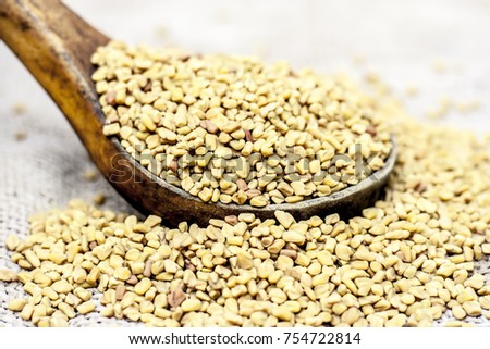 Fenugreek seeds in a wooden scoop on a gunny background.