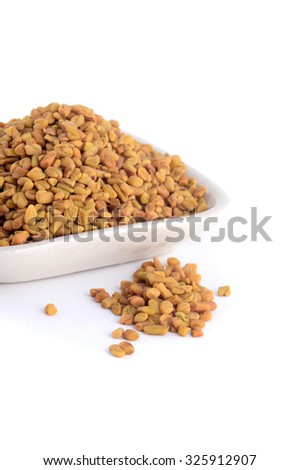 Fenugreek seeds in white plate isolated on white background