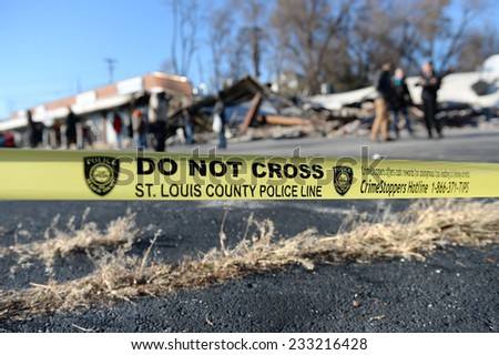 FERGUSON, MO/USA - NOVEMBER 25, 2014: Police yellow tape in front of smoldering remains of Prime Beauty Supply in Ferguson in the aftermath of riots. - stock photo