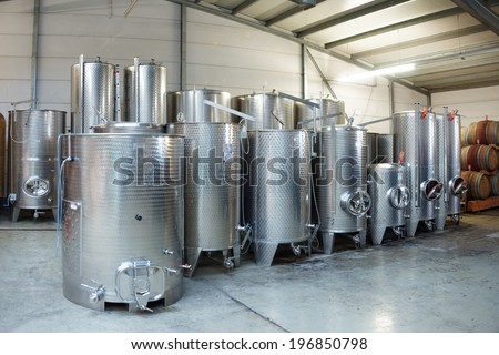 Fermentation stainless steel vats in warehouse - stock photo