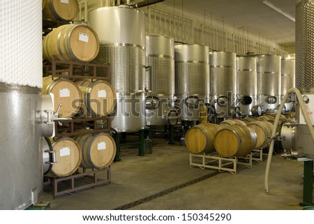 Fermentation tanks and barrels of wine in cellar - stock photo