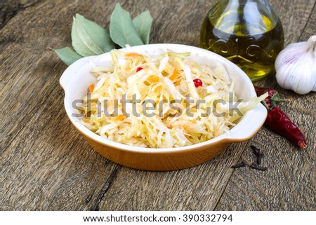 Fermented cabbage - Sauerkraut with herbs and spices on the wood background - stock photo
