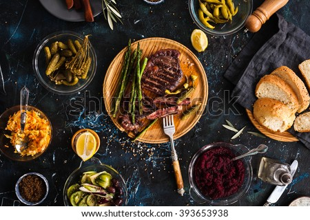 Fermented veggies and grilled meat concept. Sliced medium rare grilled beef barbecue Ribeye steak with chimichurri sauce, beet dip, marinated cucumber, red cabbage on cutting board on dark background - stock photo