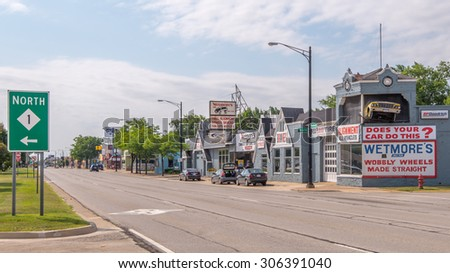 FERNDALE, MI/USA - AUGUST 13, 2015: Historic Wetmore's Complete Car Care Center and M-1 (Woodward) sign, on the Woodward Dream Cruise route. Woodward is a National Scenic Byway. - stock photo