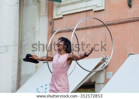 "FERRARA, Italy - August 29, 2015: BFERRARA, Italy - August 29, 2015: the artist ""The Tanik Hula Hoop's"", performing a show with hula hoop in Ferrara, during the Busker Festival"